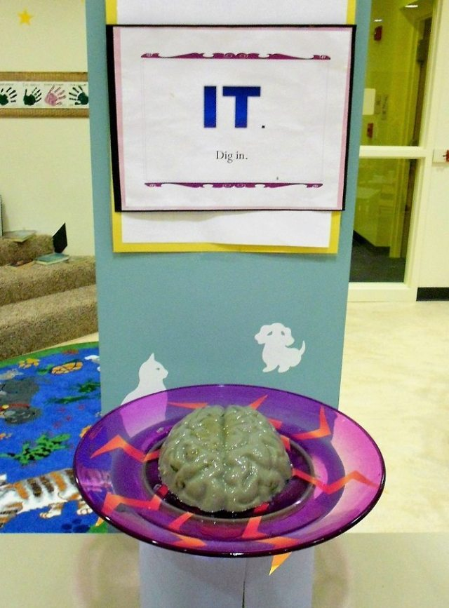"Brain-shaped gray gelatin on a purple plate with lightning bolts, with a sign reading ""IT: Dig in."""