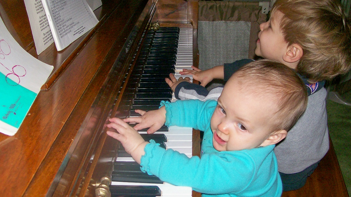 Two toddlers sitting at an upright piano, appearing to sing and play