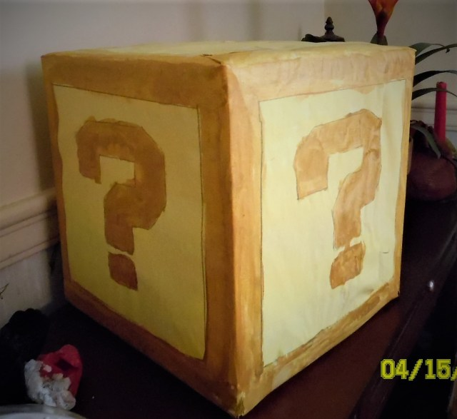 Cubical box wrapped and painted like a Mario-type mystery box, with large question marks on each surface.