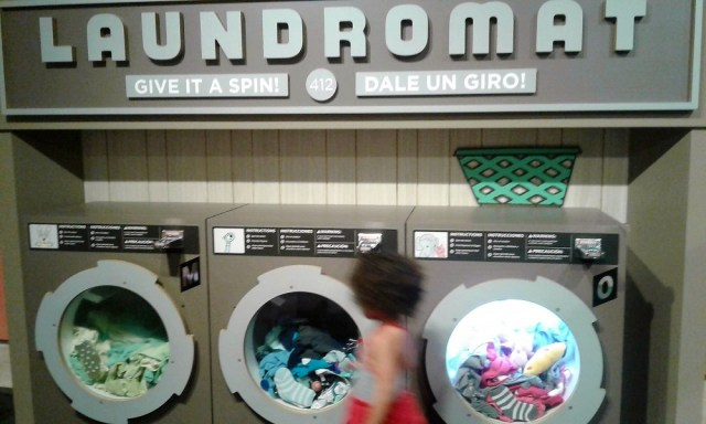 """""""Laundromat"""" display with three turnable washing machine fronts full of soft objects"""