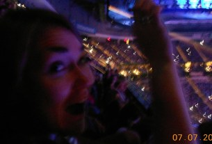 Excited woman waving a lit cell phone (the modern-day lighter) amid an arena full of other people, other lit cell phones speckling the crowd.