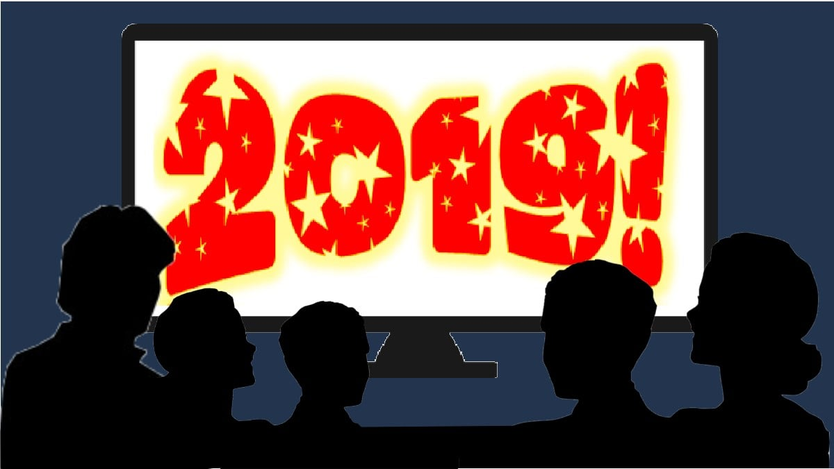 """a family of silhouettes sitting in front of a large screen tv that says """"2019!"""""""