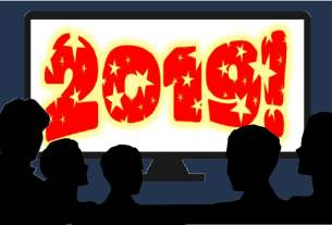 "a family of silhouettes sitting in front of a large screen tv that says ""2019!"""
