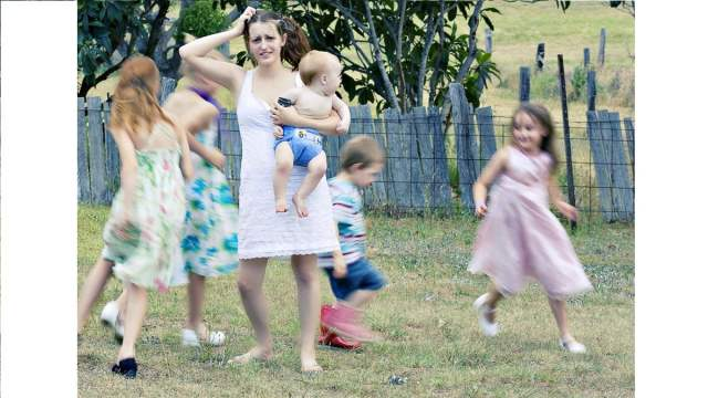 frazzled mom surrounded by blurrily running children