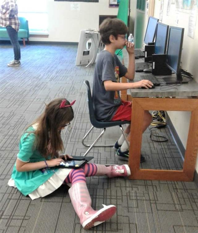 Girl in Star Butterfly costume sits on floor with a tablet beside boy at a table playing on a computer