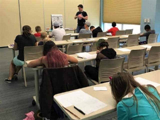Man stands before tables of a dozen kids busy drawing