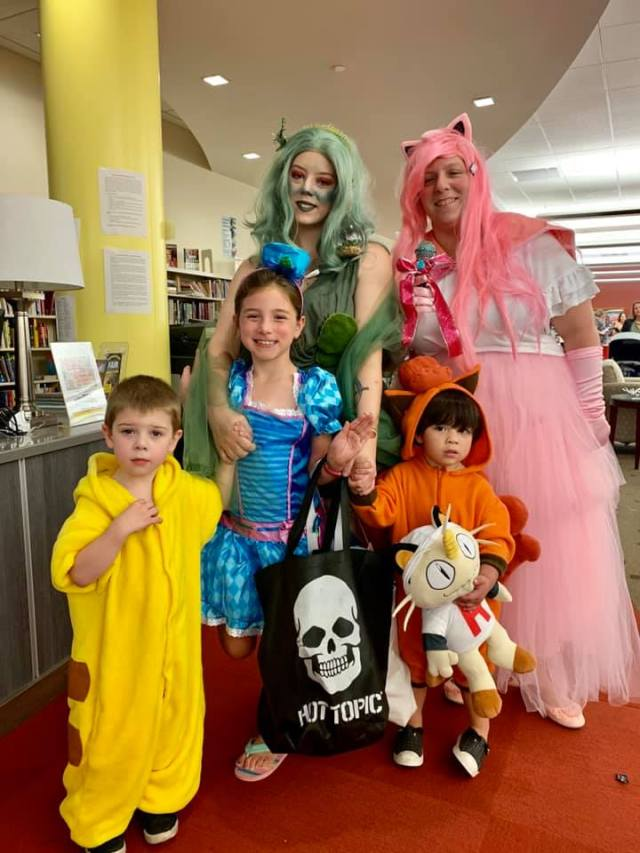 Two adults as colorful anime characters and three children of various ages in more colorful (mostly Pokemon) costumes