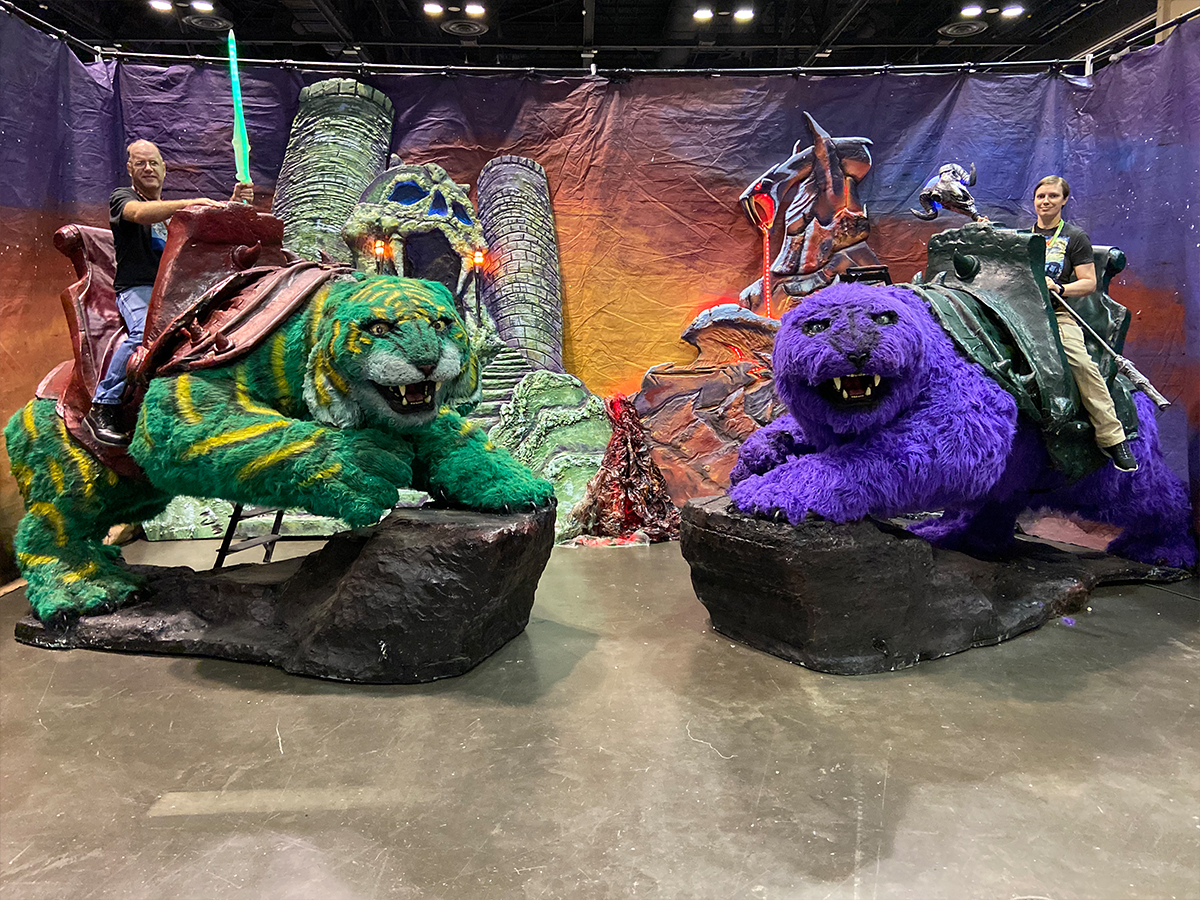 two people sitting on green Cringer from He-Man and Panthor from Skeletor