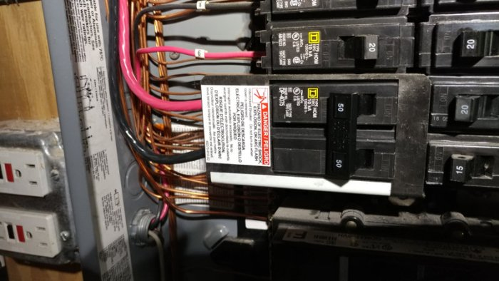 Backfeed circuit breaker installed in panel with panel cover removed