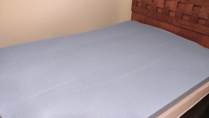 Unfolded mattress topper on top of the mattress