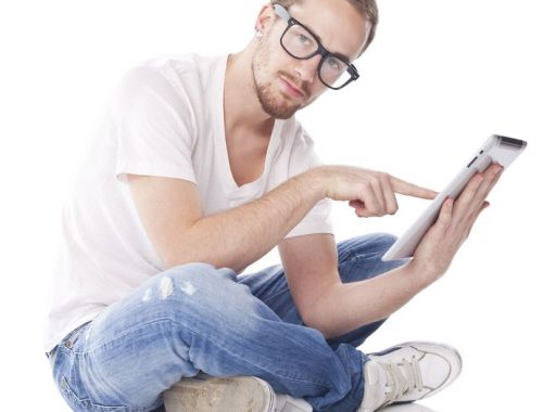 Good Looking Young Man Using Tablet Computer and sitting on floor