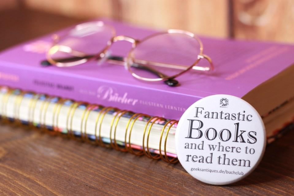 Buchclub-Button vor einem Stapel Bücher. Foto: Lilli/geek's Antiques