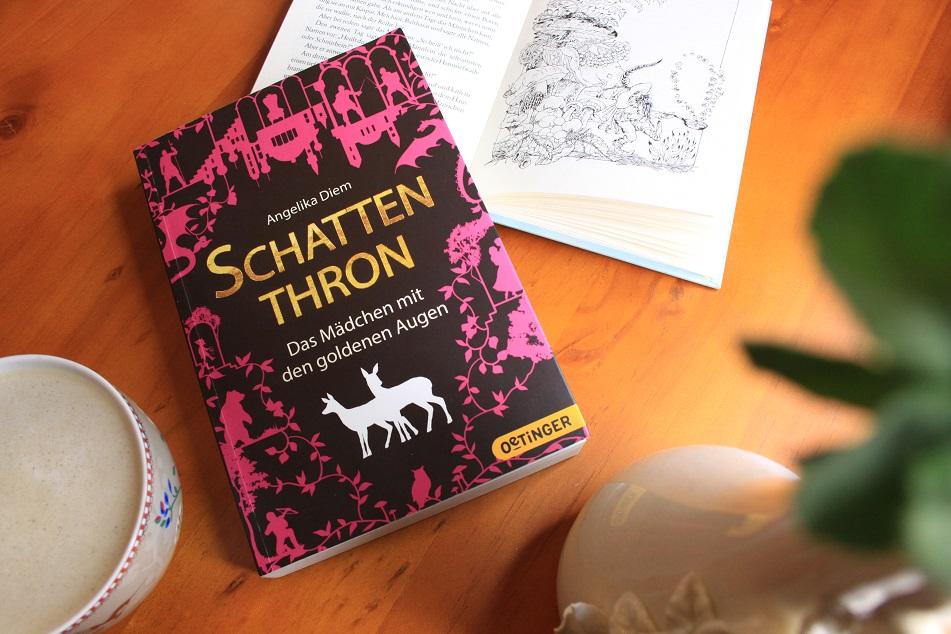 Eine Tasse Kaffee, das Buch Schattenthron von Angelika Diem und ein aufgeschlagenes Buch auf einem Tisch.