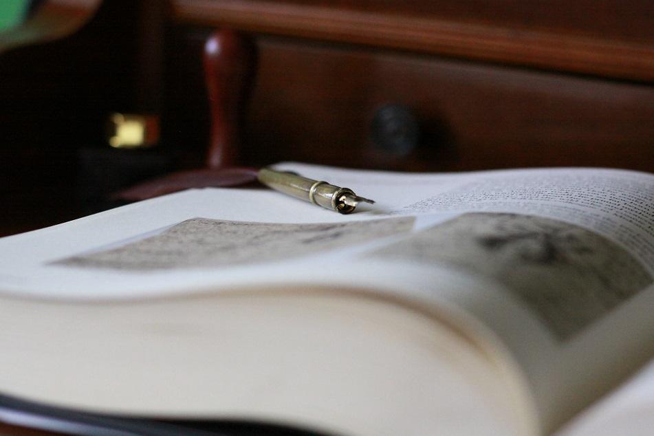 Ein aufgeschlagenes Buch aus dem Beitrag zum All Hallows Read in Deutschland auf einem Tisch mit einer Schreibfeder. Foto: geek's Antiques/Lilli