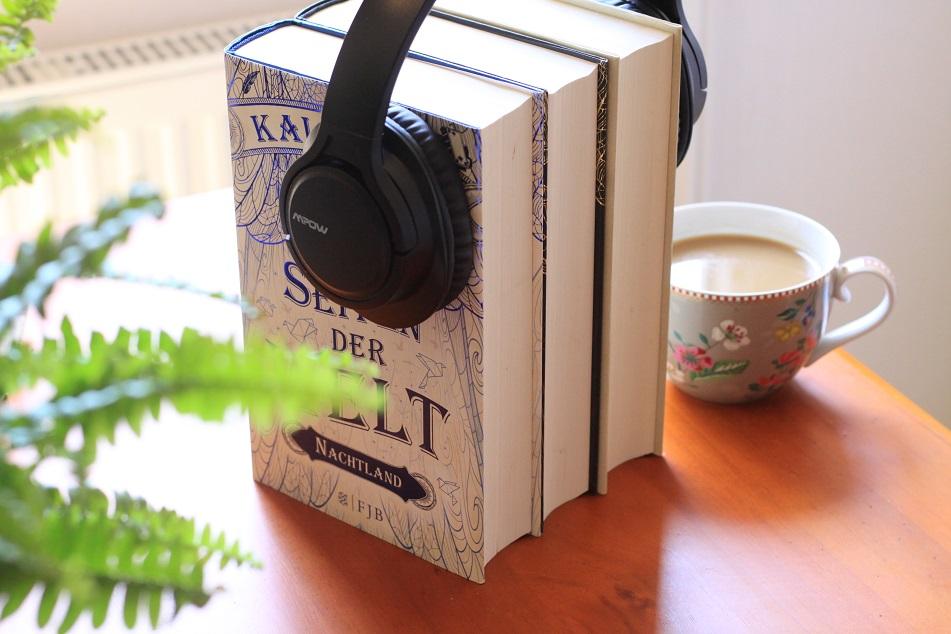 Ein Stapel Bücher mit Kopfhörern und einer Tasse Kaffee. Foto: Lilli/geek's Antiques