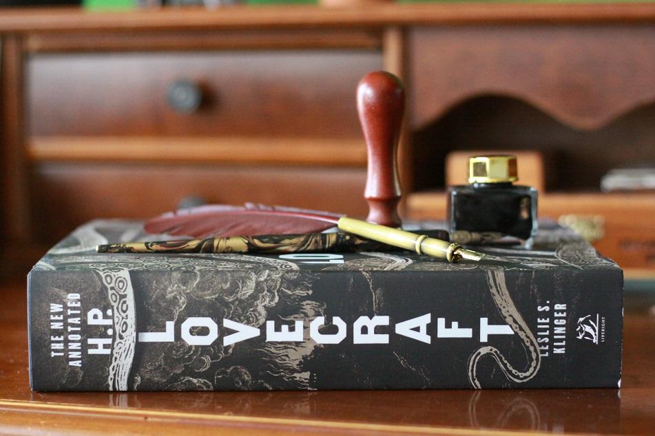 Ein Buch von H.P. Lovecraft, Schreibwerkzeug und ein Tintenfass auf einem Tisch. Foto: geek's Antiques/Lilli