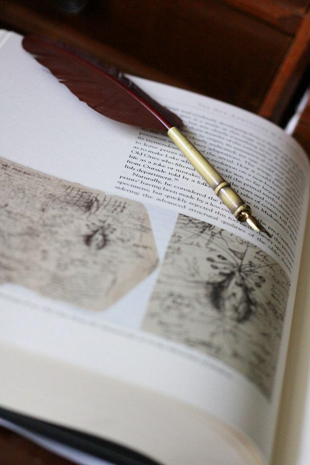 Ein Buch von H.P. Lovecraft und eine Schreibfeder auf einem Tisch. Foto: geek's Antiques/Lilli