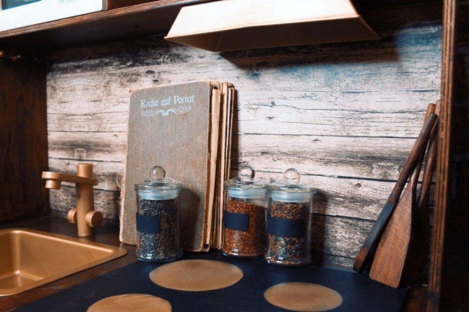 Detailansicht der Kinderküche mit Kochbuch, Gewürzen und Kochlöffeln. Foto: Lilli/geek's Antiques