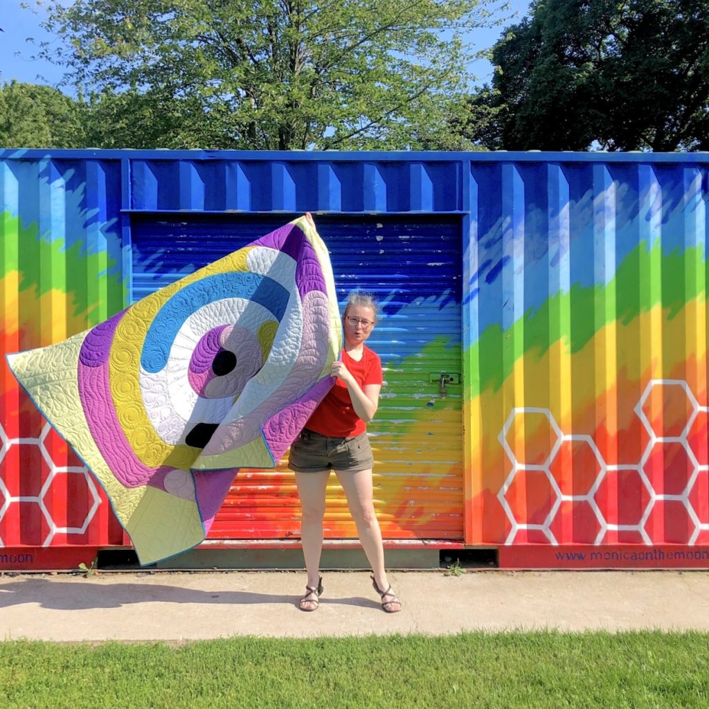 Orbital quilt by geeky bobbin in front of rainbow mural