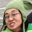 An woman smiling, wearing glasses and a green knit Yoda hat