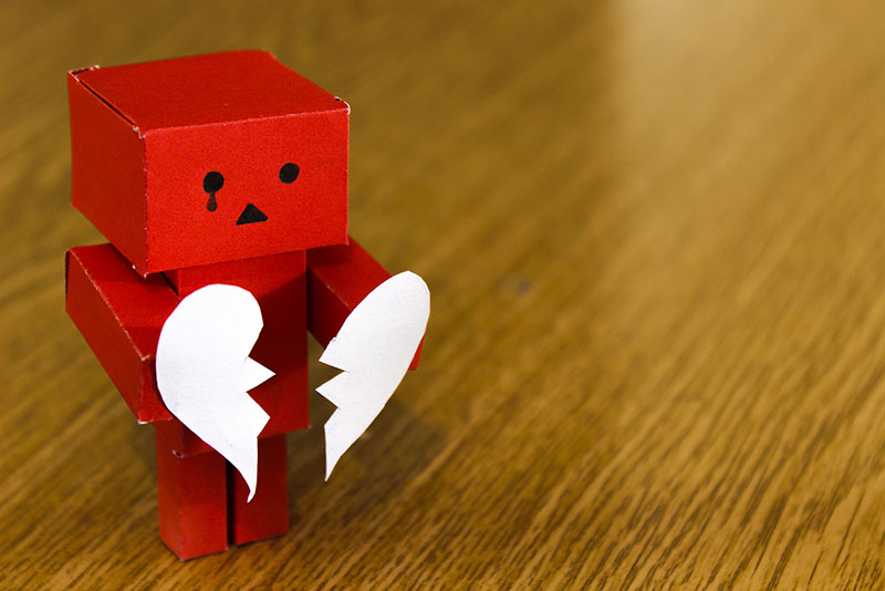 Red, tiny robot made out of paper, a black tear from his right eye, holding a paper heart that's been torn in half