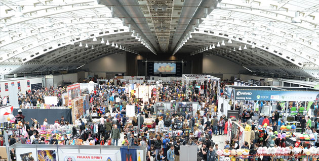 Aerial shot of a convention hall packed with people looking at booths