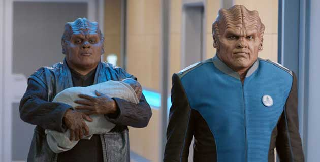 Bortus and his partner walking down a hallway, a baby in his arms. They look like Klingons