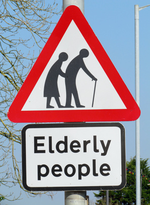 British elderly people crossing road warning sign.