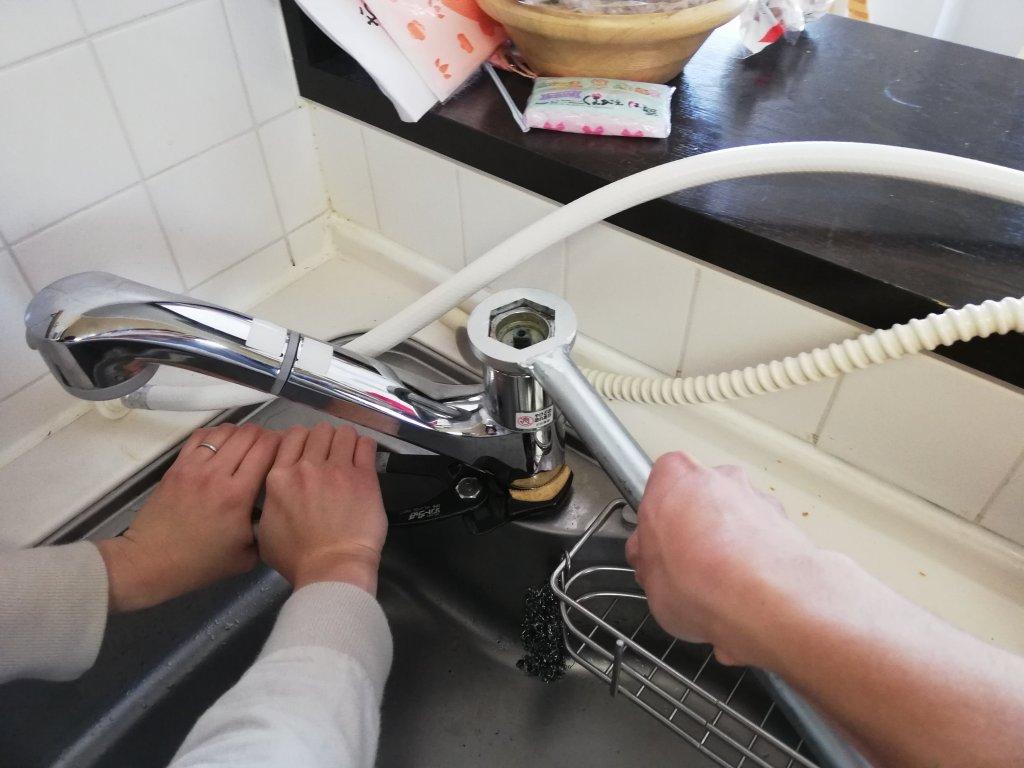 キッチンの水栓のカバーナットを夫婦2人がかりで開ける