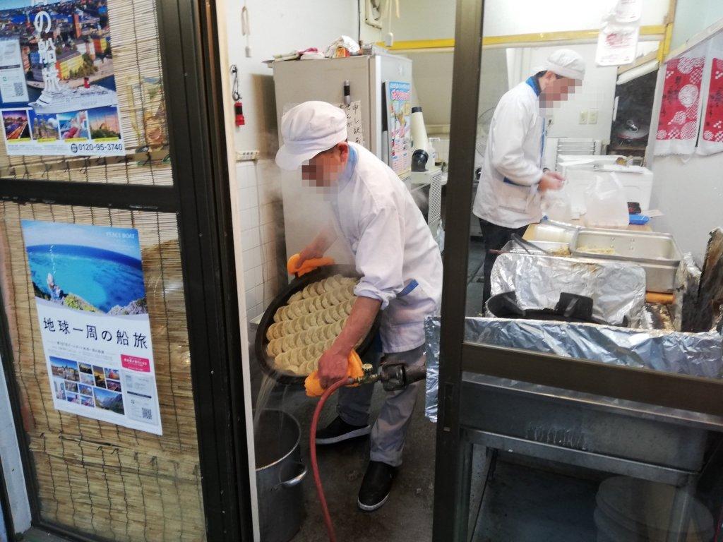 飯手慣れた手つきで餃子を焼く塚精肉店のスタッフさん