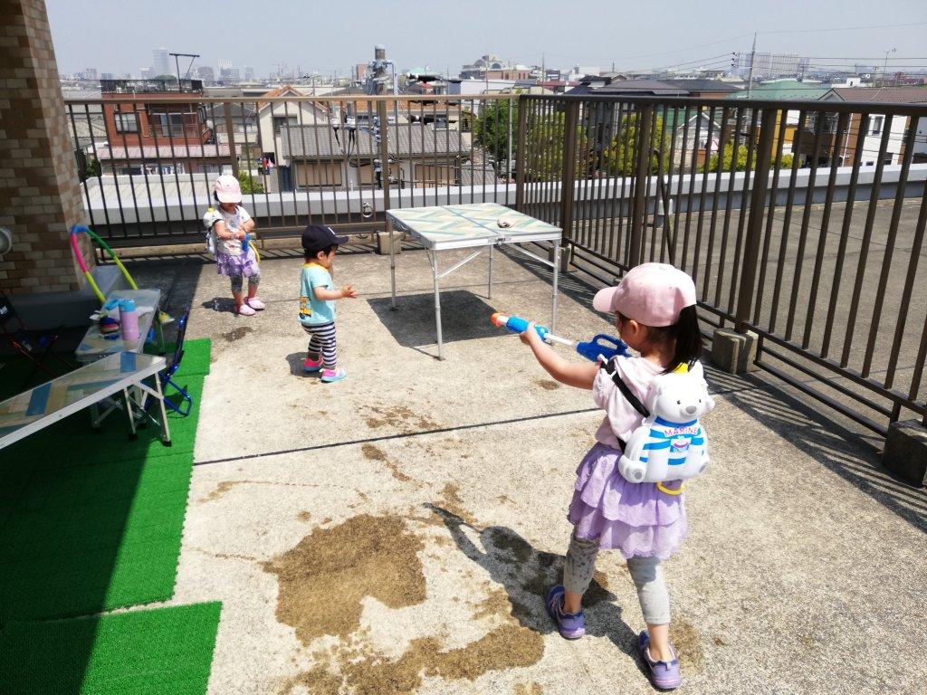 バルコニーで水鉄砲で遊ぶ子供たち