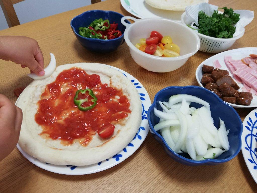 業務スーパーの冷凍ピザ生地に野菜を盛り付ける