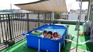 バルコニーの大型家庭用プールで遊ぶ子供たち