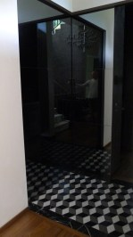 "This entry, featuring a marble ""tumbling block"" pattern, serves to re-orient the visitor into the alternate reality of this house, and serves as a formal de-cloaking room, with full closet behind the mirror door."