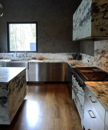 Pavonazzetto marble and stainless steel. Venetian plaster on the walls. A custom stainless apron sink is served by twin Karbon faucets.