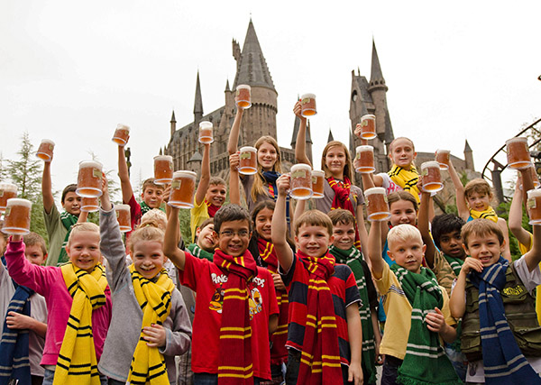 """On Wednesday, December 12, 2012, Universal Orlando Resort and its guests celebrated the five-millionth serving of Butterbeer - the incredibly popular themed beverage sold within The Wizarding World of Harry Potter. To mark the moment, Universal Orlando gave away one thousand Butterbeers to guests, including these young fans who sported """"Butterbeer mustaches"""" after taking a sip. (C) 2012 Universal Orlando Resort. All rights reserved. The Wizarding World of Harry Potter(TM) Butterbeer(TM) and beverage HARRY POTTER, characters, names and related indicia are trademarks of and (C) Warner Bros. Entertainment Inc. Harry Potter Publishing Rights (C) JKR. (s12). (PRNewsFoto/Universal Orlando Resort)"""
