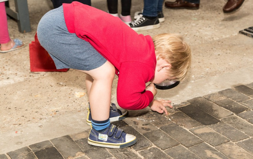 A young boy investigating the Grade II Long Shop wooden floor blocks.