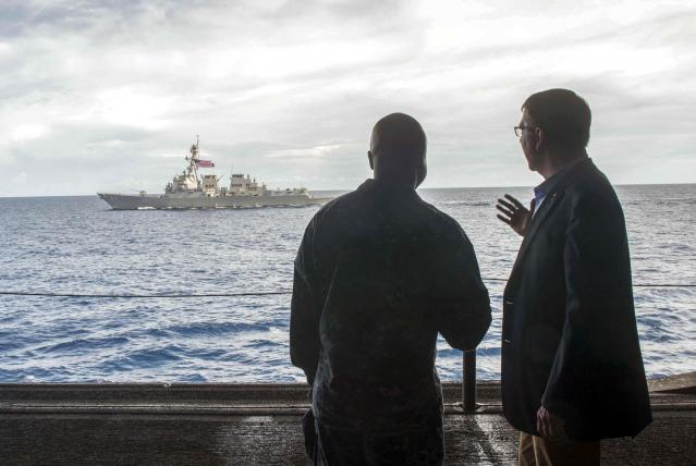 U.S. Secretary of Defense Carter speaks with U.S. Navy Cmdr. Francis aboard the USS Theodore Roosevelt in South China Sea