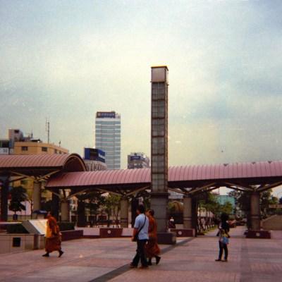 monks walking along a train station