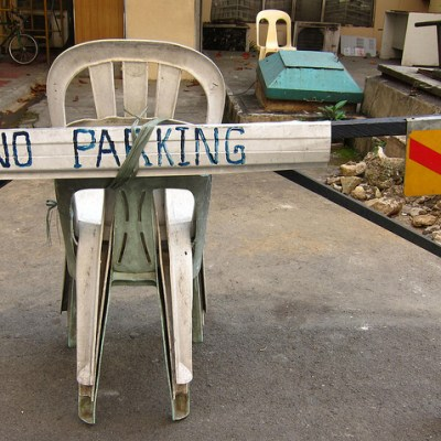 no parking sign above monobloc chairs