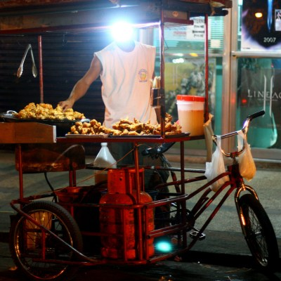 food stall vendor on a pedicab whose face is obscured by a light bulb
