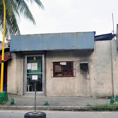 small office with blue top standing alone below a coconut tree