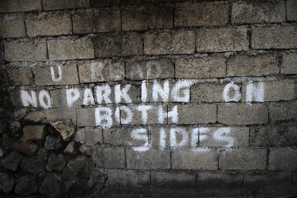 handwritten No Parking written on hollow block wall