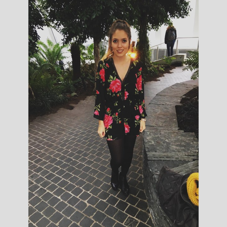 """A woman wearing a black play-suit with pink flowers all over and green leaves, paired with black tights and black boots. The woman has her dip dyed blonde/brown hair tied up and is standing inside """"Sky garden"""" in London."""