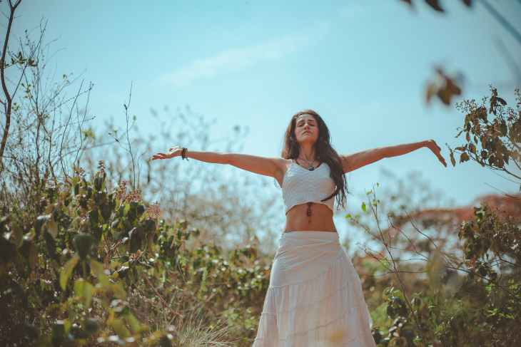 A woman wearing a white crop top and white long skirt with her eyes shut and arms out to the side of her in nature.