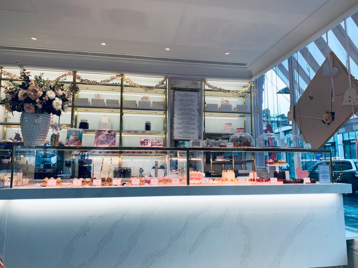 """Inside the London, Chelsea cafe """"Peggy Porschen"""" counter and decoration, showing a selection of cakes and treats."""