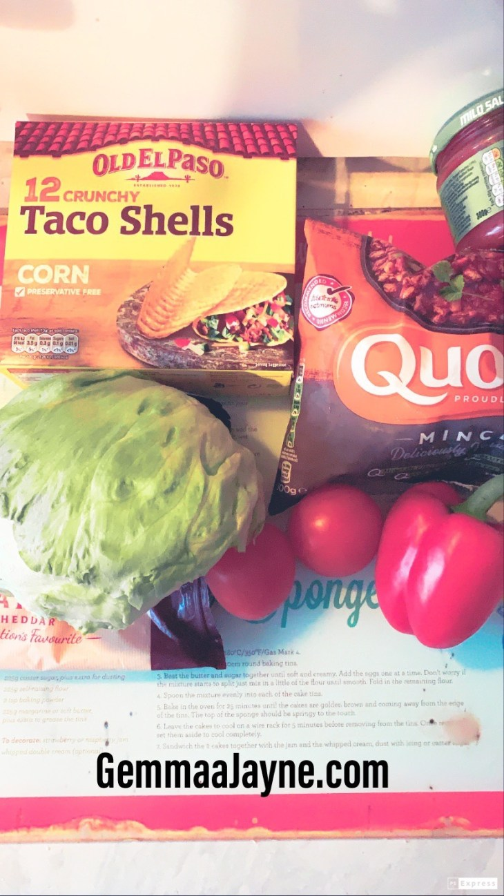 A box of taco shells, with quorn mince, salsa, lettuce, peppers and tomatoes on a chopping board.