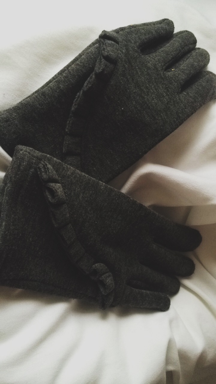 A pair of grey gloves with a design down the side.