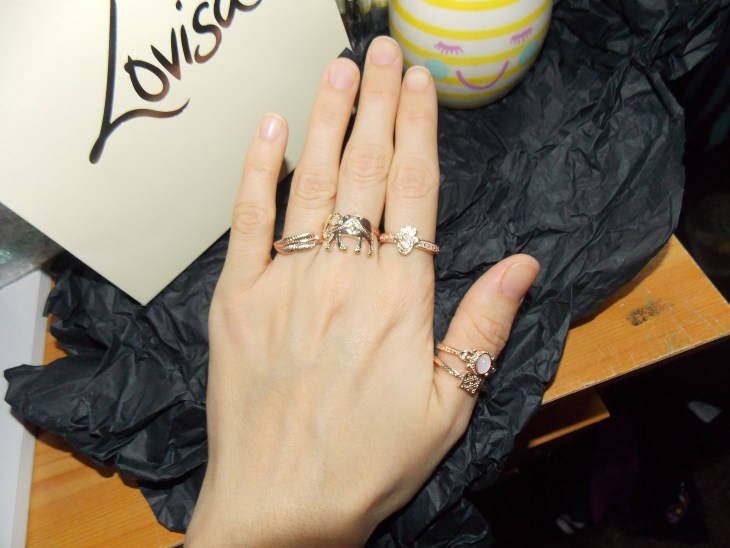 """A hand wearing a collection of rose gold rings on all fingers but the pinky. Black tissue paper as background and a stipey yellow and white pot with a pink smiley face on it, and the brand """" Lovisa"""" gift back in the back."""