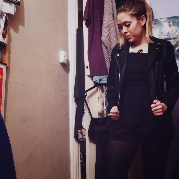 A woman wearing a black play-suit with a black and white striped top with tights and a leather jacket in her bedroom.